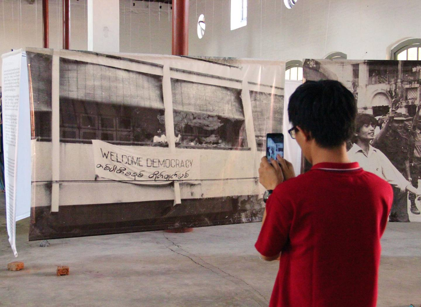 A visitor to an exhibition at the Secretariat building photographs an iconic image. Photo by Stephen Starr