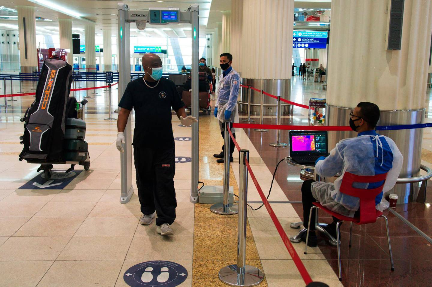 A passenger wearing a mask due to the coronavirus pandemic passes through a temperature screening at Dubai International Airport's Terminal 3 in Dubai, United Arab Emirates, Wednesday, June 10, 2020. The coronavirus pandemic has hit global aviation hard, particularly at Dubai International Airport, the world's busiest for international travel, due to restrictions on global movement over the virus. (AP Photo/Jon Gambrell)