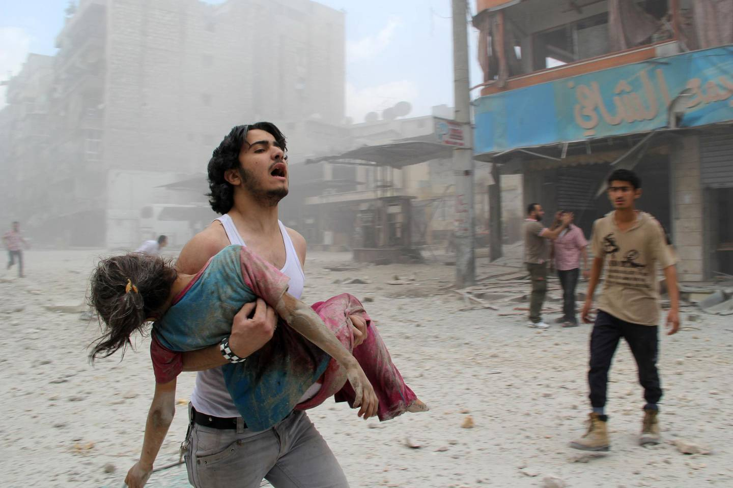 EDITORS NOTE: Graphic content / (FILES) In this file photo taken on June 3, 2014, a man carries a young girl who was injured in a reported barrel-bomb attack by government forces, in Kallaseh district in the northern city of Aleppo. As it enters its tenth year, the war in Syria is anything but abating as foreign powers scrap over a ravaged country where human suffering keeps reaching new levels. / AFP / BARAA AL-HALABI