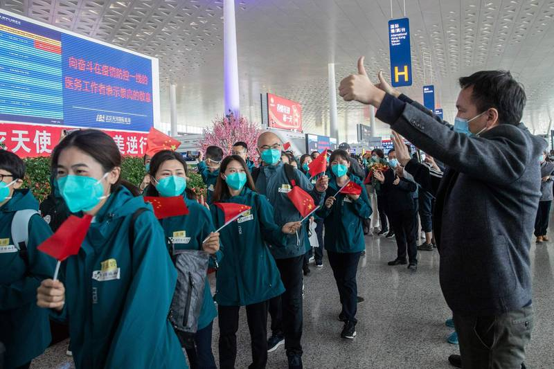 Local volunteers gesture as medical staff members (in green) from Peking Union Medical College Hospital leave at Tianhe airport in Wuhan in China's central Hubei province on April 15, 2020. Medical staff from Peking Union Medical College Hospital is the last medical assistance team from other provinces leaving Wuhan after helping with the COVID-19 coronavirus recovery effort. - China OUT  / AFP / STR