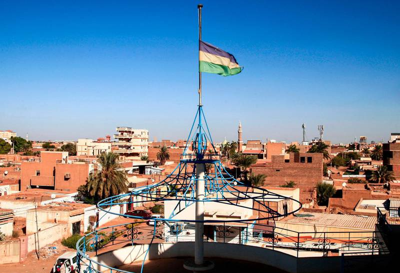 This picture taken on November 28, 2020 from the Sudanese capital's twin city of Omdurman shows a view of the blue-yellow-green tricolour flag used at the time of Sudan's independence flying at the house of Sayyid Ismail al-Azhari, who served as the first prime minister of independent Sudan from 1954 to 1956, and as President of Sudan from 1965 until his overthrow by a military coup in 1969. In Syria, Libya and more recently Sudan, Arab revolutionaries have begun brandishing old independence-era flags, attacking newer ones as symbols of the dictatorships they want to topple. Sudan's flag has three horizontal bands: blue for the Nile river, yellow for the desert and green for agriculture. Then president Gaafar al-Nimeiri dropped it in 1970, in favour of the colours of Arab nationalism. / AFP / Ebrahim HAMID