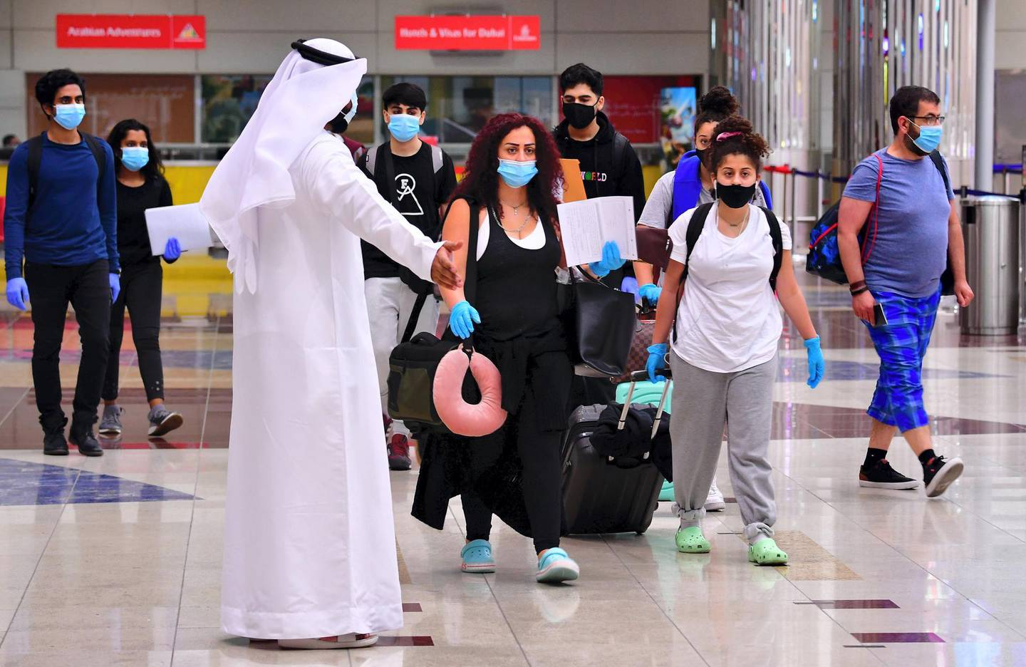 Tourists arrive at Dubai airport in the United Arab Emirates on July 8, 2020, as the country reopened its doors to international visitors in the hope of reviving its tourism industry after a nearly four-month closure. (Photo by GIUSEPPE CACACE / AFP)