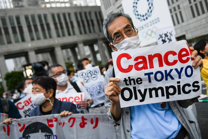 Demonstrators hold placards in front of the Tokyo Metropolitan government building during an anti-Olympic protest in Tokyo, Japan, on Wednesday, June 23, 2021. More evidence emerged that the Japanese publics opposition to next months Tokyo Olympics is losing steam, according to a series of media polls published roughly one month before the opening ceremony. Photographer: Noriko Hayashi/Bloomberg