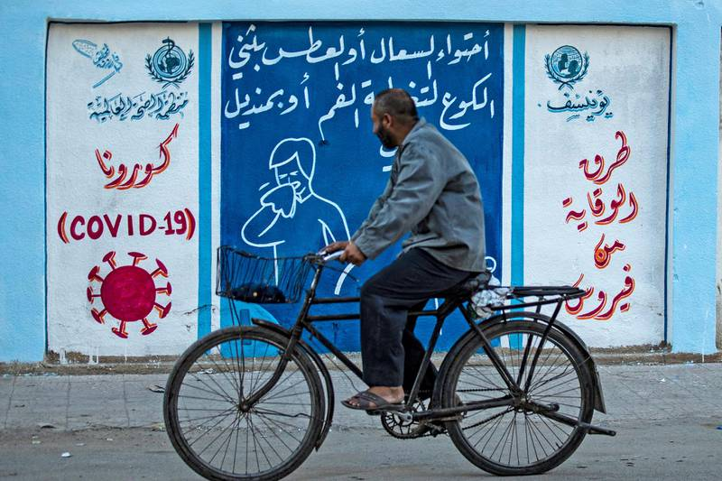 A Syrian man rides a bicycle past a mural painted as part of an awareness campaign by the United Nations International Children's Emergency Fund (UNICEF) and World Health Organization (WHO) intitative, bearing instructions on protection from COVID-19 in the Kurdish-majority city of Qamishli of Syria's northeastern Hasakeh province on August 16, 2020, after a spike in infections in the area. (Photo by Delil SOULEIMAN / AFP)