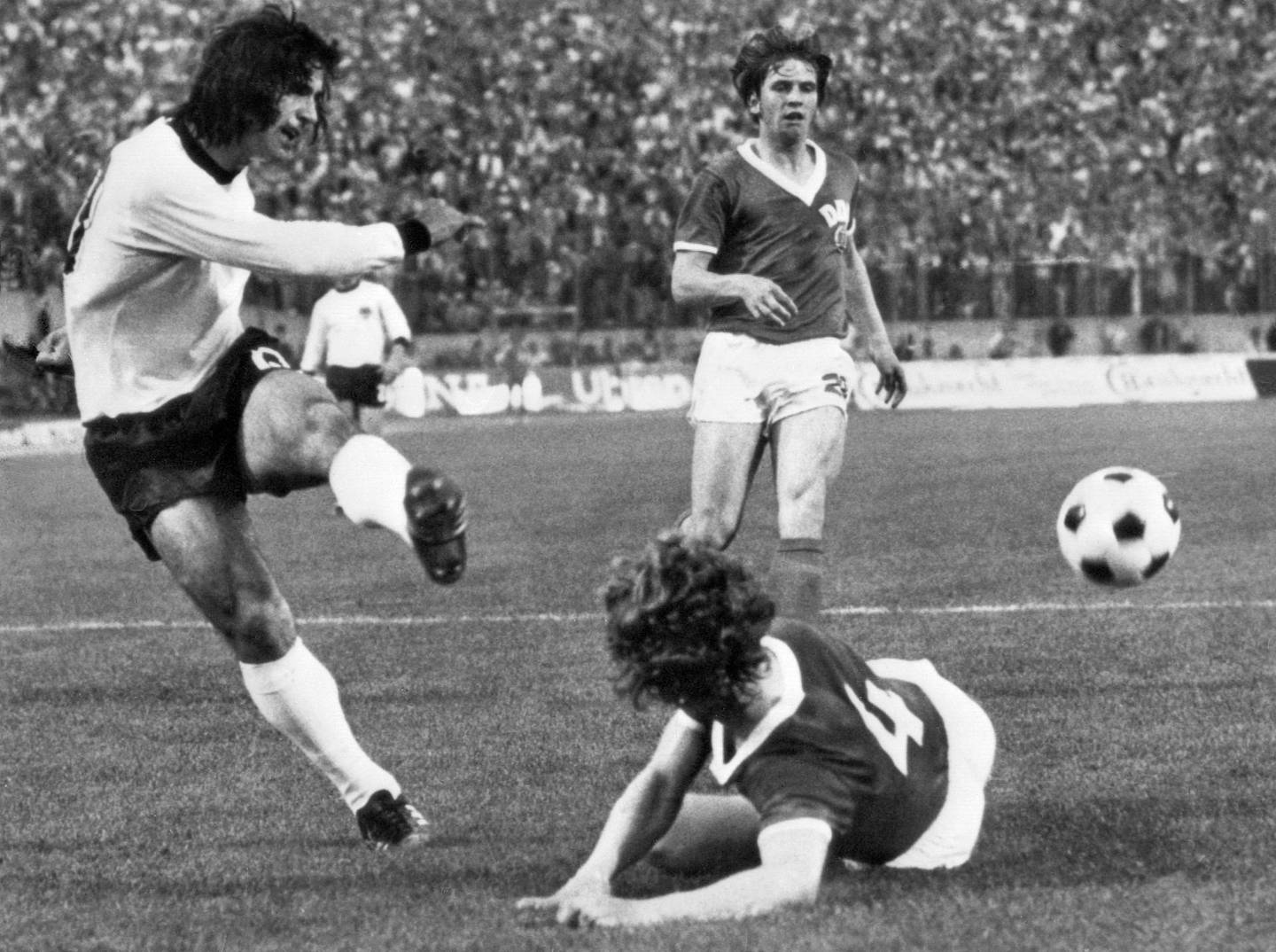 (FILES) In this file photo taken on June 22, 1974 West German forward Gerd Müller (L) kicks the ball past East German defender Konrad Weise (R) as forward Martin Hoffmann looks on during the World Cup first round match between East Germany and West Germany in Hamburg.   / AFP / STAFF