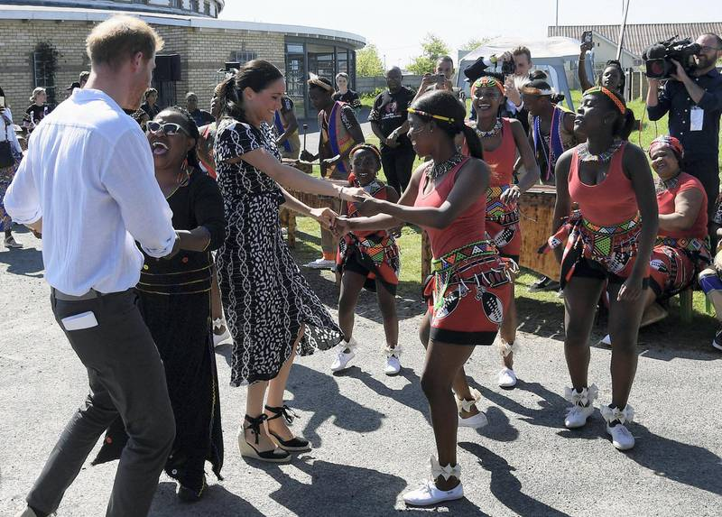 The Duke and Duchess of Sussex, Prince Harry and his wife Meghan, dance during a Justice Desk initiative in Nyanga township, on the first day of their African tour in Cape Town, South Africa, September 23, 2019. REUTERS/Toby Melville