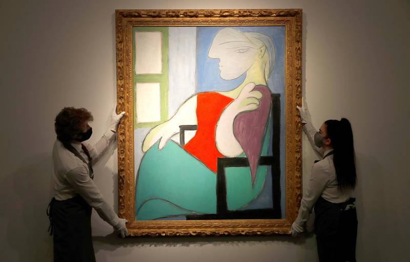 """Employees pose for a photograph with """"Femme Assise Pres d'Uune Fenetre (Marie-Therese)"""" by Pablo Picasso at Christie's gallery prior to the New York spring season of evening sales, in London, Britain, April 22, 2021. REUTERS/Peter Nicholls   NO RESALES. NO ARCHIVES."""