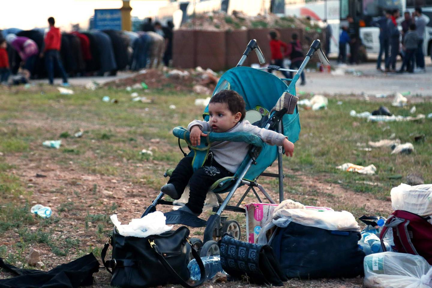 A Syrian child waits in a stroller as buses with Jaish al-Islam fighters and their families on board arrive from their former rebel bastion of Douma in Eastern Ghouta at the Abu al-Zindeen checkpoint controlled by Turkish-backed rebel fighters near the Syrian town of al-Bab in the northern Aleppo province, on April 14, 2018. The Syrian army on April 14 declared that all anti-regime forces had left Eastern Ghouta, nearly two months into a blistering offensive on the rebel enclave. / AFP PHOTO / Nazeer al-Khatib