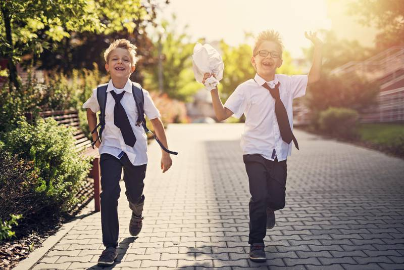 Two happy little boys walking in residential area walkway. Little brothers are going to school in the morning. Getty Images
