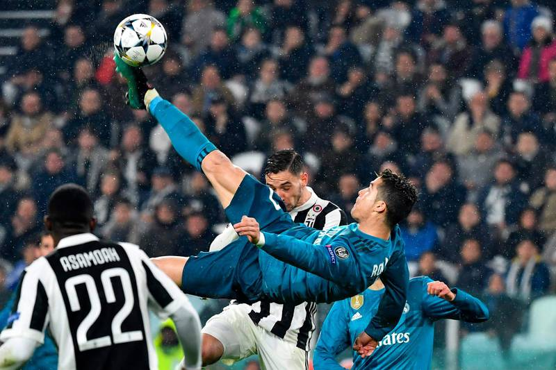 """(FILES) In this file photo taken on April 03, 2018 Real Madrid's Portuguese forward Cristiano Ronaldo (C) overhead kicks and scores during the UEFA Champions League quarter-final first leg football match between Juventus and Real Madrid at the Allianz Stadium in Turin on April 3, 2018. Real Madrid announced on July 10, 2018 the transfer of Cristiano Ronaldo to Italy's Juventus, with the Portuguese superstar saying the time had come """"for a new stage"""" in his life. / AFP / Alberto PIZZOLI"""
