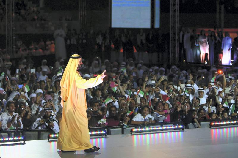Ruler of Dubai Sheikh Mohammed Bin Rashid al-Maktoum salutes the crowd as he takes part in celebrations near Dubai's Burj Khalifa, the world's tallest tower, on December 1, 2013, marking the United Arab Emirates national day and the victory for Dubai to host the 2020 World Expo. A jubilant Dubai hopes that hosting the world's five-yearly trade fair in 2020 will draw new investment to an economy still recovering from a debt crisis that required a bailout by Abu Dhabi PHOTO/MARWAN NAAMANI (Photo by MARWAN NAAMANI / AFP)