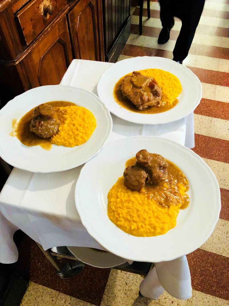 Three plates of saffron risotto and ossobuco, the typical dish of Milan, Italy