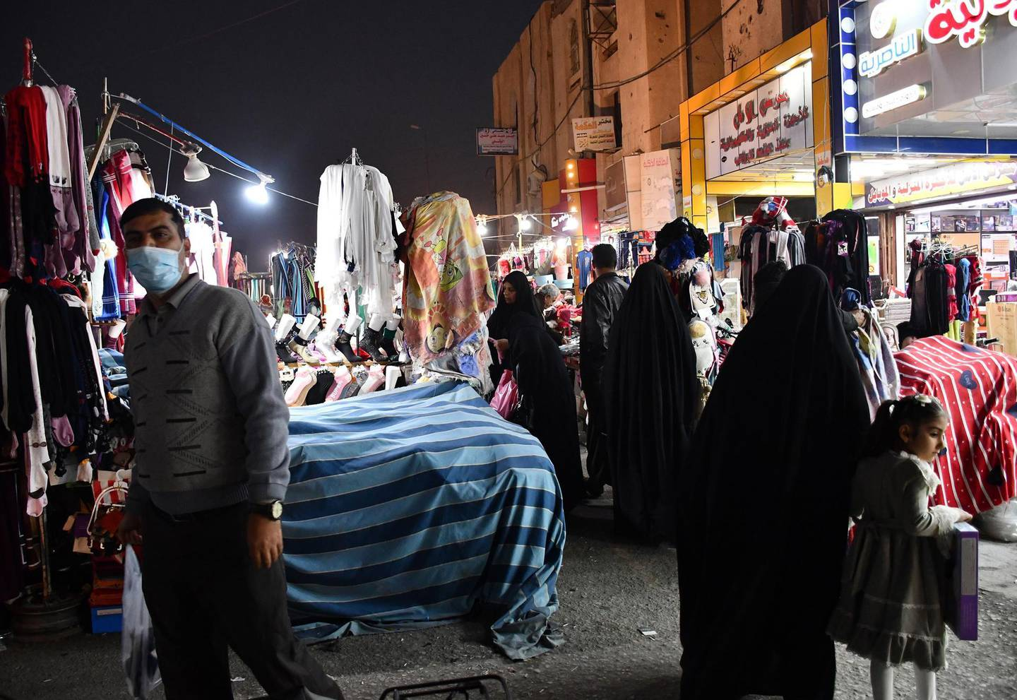A man wearing a face mask due to the novel coronavirus walks in a market in the southern Iraqi city of Nasiriyah in the Dhi Qar province, on December 20, 2020.  A year of economic agony for pandemic-hit and oil-reliant Iraq is drawing to a close, but a draft 2021 budget involving a hefty currency devaluation could bring more pain for citizens. Iraq, which relies on oil sales to finance 90 percent of its budget, projects that its economy has shrunk by 11 percent this year, while poverty doubles to 40 percent of the country's 40 million residents. / AFP / Asaad NIAZI