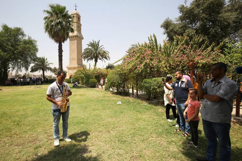 Iraqis film a man playing the saxophone in the park near al-Mutanabi Street in Baghdad on August 18, 2017. (Photo by AHMAD AL-RUBAYE / AFP)