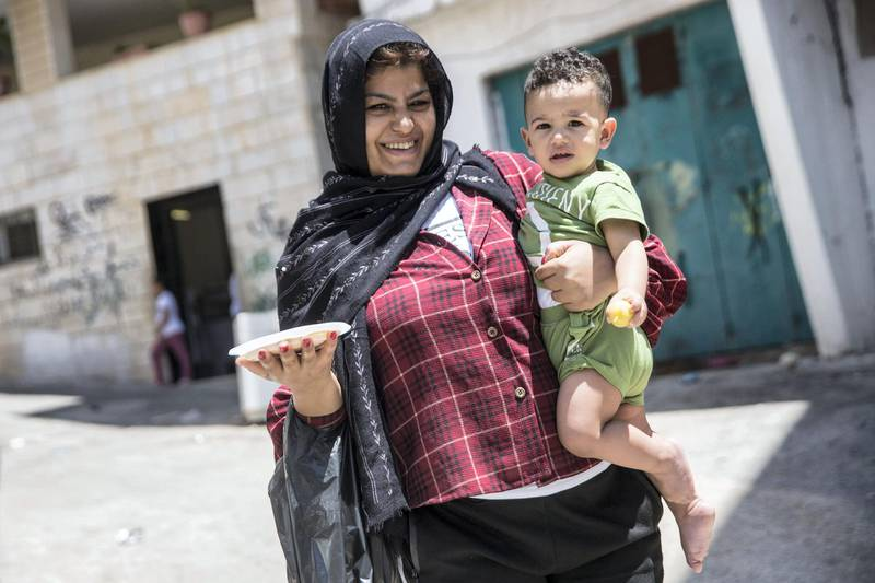Palestinian woman Amman Rajara ,20, carries a plate of humous and a child in the Aida refugee camp near the city of Bethlehem on June 23,2019.Photo by Heidi Levine for The National