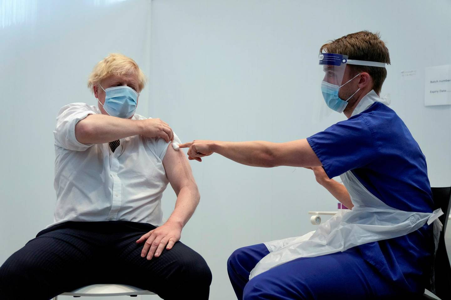 Britain's Prime Minister Boris Johnson holds up his sleeve after receiving his second dose of the AstraZeneca coronavirus disease (COVID-19) vaccine from James Black, at the Francis Crick Institute in London, Britain June 3, 2021. Matt Dunham/Pool via REUTERS