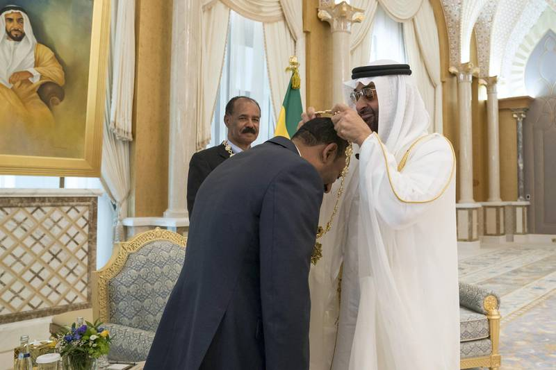 ABU DHABI, UNITED ARAB EMIRATES - July 24, 2018: HH Sheikh Mohamed bin Zayed Al Nahyan Crown Prince of Abu Dhabi Deputy Supreme Commander of the UAE Armed Forces (R), presents a Zayed Medal to HE Dr Abiy Ahmed, Prime Minister of Ethiopia (L), during a reception at the Presidential Palace. Seen with HE Isaias Afwerki, President of Eritrea (back C) ( Mohamed Al Hammadi / Crown Prince Court - Abu Dhabi ) ---