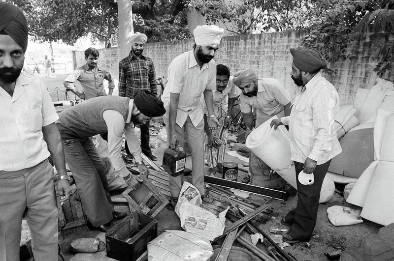 Members of the Indian Sikh community, whose house were attacked, burned and looted the past days by mobs of Hindus are seen as they collect their looted property in a Delhi police station, Nov. 6, 1984. Life is returning to normal after heavy riots that followed the assassination of Prime Minister Indira Gandhi. (AP Photo/Peter Kemp)