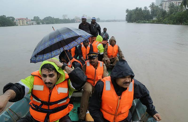 Indian fire and rescue personnel evacuate local residents in an boat flooded following monsoon rains at Aluva, in the Indian state of Kerala, on August 16, 2018. - The death toll from floods in India's tourist hotspot of Kerala increased to 77 on August 16, as torrential rainfall threatened new areas, officials told AFP. (Photo by - / AFP)