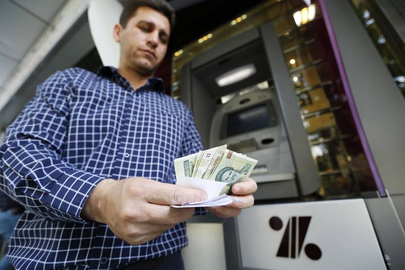 A man withdraws Iranial Rials from an automated teller machine in the capital Tehran on July 31, 2018.  Iran's currency traded at a fresh record-low of 119,000 to the dollar on today, a loss of nearly two-thirds of its value since the start of the year as US sanctions loom. / AFP PHOTO / ATTA KENARE