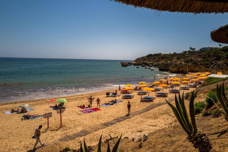 Beachgoers relax on Oura Beach in Albufeira, Portugal, on Saturday, May 29, 2021. Portugal is likely to raise its economic growth forecast for this year to close to 5% as tourists help boost the recovery and Europe's Covid-19 vaccination campaign advances. Photographer: Jose Sarmento Matos/Bloomberg