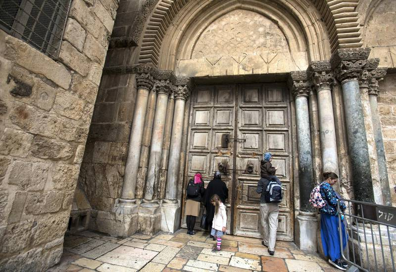 Christian pilgrims pray by the closed wooden doors Church of the Holy Sepulchre in the Old City of Jerusalem on Monday February 26,2018.The Church of the Holy Sepulchre  remained closed for a second day after church leaders in Jerusalem closed it to protest against Israeli's announced plans by the cityÕs municipality earlier this month to collect property tax (arnona) from church-owned properties on which there are no houses of worship. (Photo by Heidi Levine for The National).
