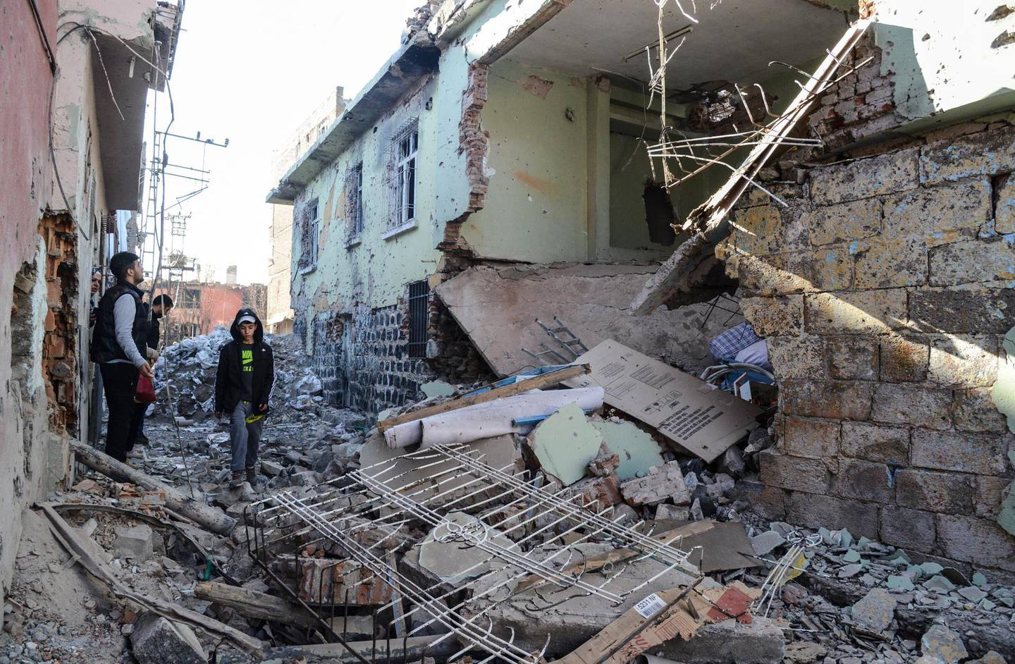 Boys walk among rubble and damaged buildings in the Sur district in Diyarbakir on December 11, 2015. A policeman was killed on December 9, 2015 by sniper fire as he tried to defuse an explosive device in the Sur district of Diyarbakir province, which has been under military curfew for eight days. Turkey has been waging a relentless offensive against PKK strongholds in the southeast of the country and in northern Iraq following the collapse in July of a two-year truce with rebels.     / AFP PHOTO / ILYAS AKENGIN