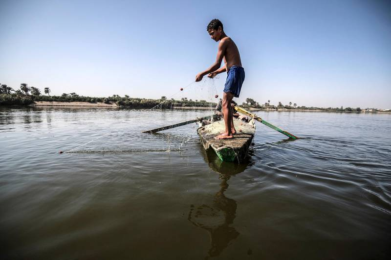 A young Egyptian fisherman pulls his net in the River Nile in Gabal al-Tear village near Minya city, some 265 km south of the Egyptian capital Cairo, on November 13, 2019. - Egypt has for years been suffering from a severe water crisis that is largely blamed on population growth. Mounting anxiety has gripped the already-strained farmers as the completion of Ethiopia's gigantic dam on the Blue Nile, a key tributary of the Nile, draws nearer. Egypt views the hydro-electric barrage as an existential threat that could severely reduce its water supply. But Ethiopia insists that Egypt's water share will not be affected. (Photo by Khaled DESOUKI / AFP)