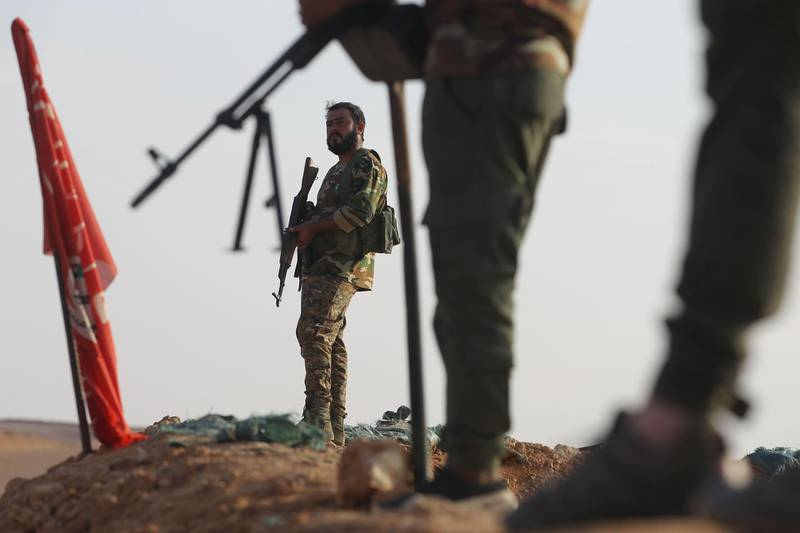 (FILES) In this file photo taken on November 12, 2018 an Iraqi Shiite fighter of the Hashed al-Shaabi paramilitary force secures the border in al-Qaim in the Anbar province, opposite Albu Kamal in Syria's Deir Ezzor region.  An air strike killed 26 fighters of Iraqi paramilitary group Hashed al-Shaabi in eastern Syria after a deadly attack on US-led coalition troops in Iraq, a war monitor said on March 12, 2020. Updating its toll for the Marcg 11 strike, the Britain-based Syrian Observatory for Human Rights said it was probably carried out by the coalition. The coalition did not immediately provide comment. Before the strike near the border town of Albu Kamal, rockets were fired at a military base north of Baghdad hosting coalition troops, killing two Americans and one Briton.  / AFP / AHMAD AL-RUBAYE