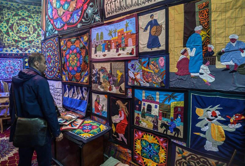 An Egyptian man looks at wall hangings at his shop in Cairo's Khayamia Street, or the Street of Tent-makers, on December 18, 2018. Along the sides of the roofed street of Khayamiya, or the Street of Tent-makers, dozens of craftsmen's shops have drawn foreign visitors for years until the 2011 uprising toppled longtime ruler Hosni Mubarak after which business has slowed to a trickle. The centuries-old art of Khayamiya, belived to have emerged during the Fatimid dynasty (10th-12th century AD), goes back to the time of travelling caravans, when huge tent pavilions were used as shields from the desert's searing sun. / AFP / Mohamed el-Shahed