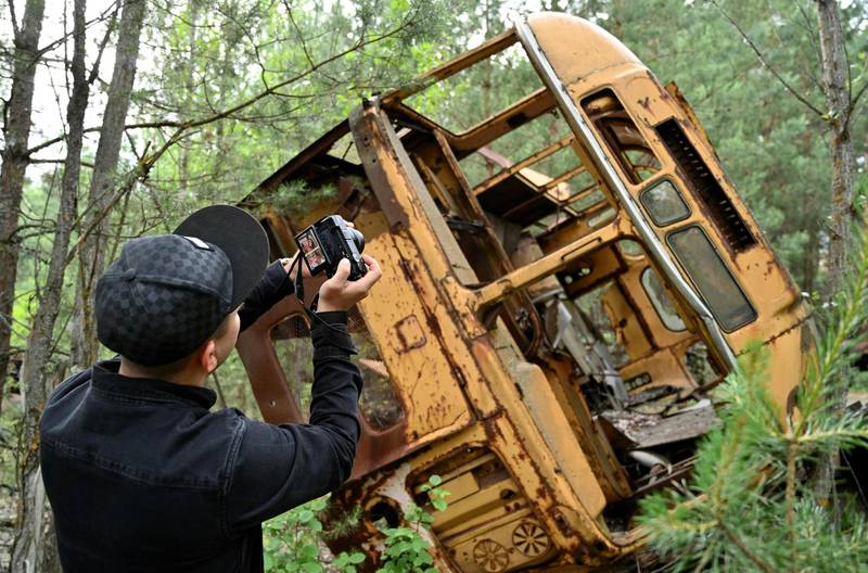 """TOPSHOT - A visitor takes a picture at a wreckage of a bus in the ghost city of Pripyat during a tour in the Chernobyl exclusion zone on June 7, 2019. HBO's hugely popular television series """"Chernobyl"""" has renewed interest around the world on Ukraine's 1986 nuclear disaster with authorities reporting a 30% increase of tourist demands to visit the affected area and tourist operators forecasting that number of tourists visiting the site may double this year up to 150.000 persons / AFP / Genya SAVILOV"""