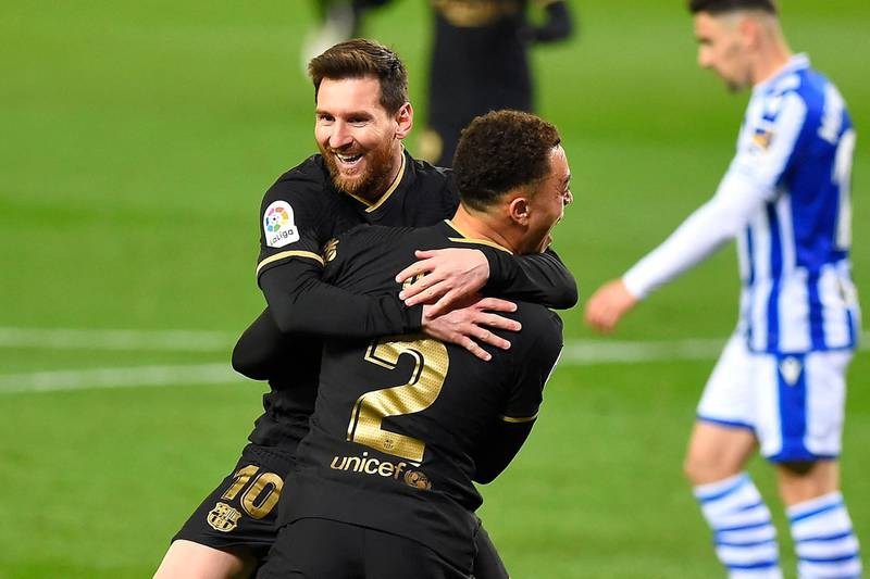 Barcelona's Barcelona's US defender Sergino Dest celebrates with Barcelona's Argentinian forward Lionel Messi (back) after scoring a goal during the Spanish League football match between Real Sociedad and Barcelona at the Anoeta stadium in San Sebastian on March 21, 2021. / AFP / ANDER GILLENEA