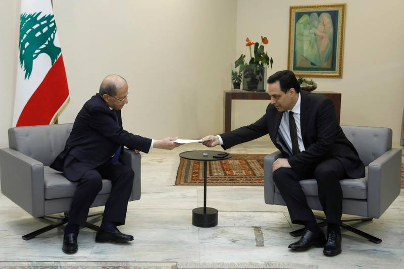 """In this photo released by Lebanon's official government photographer Dalati Nohra, Lebanese President Michel Aoun, left, receives a letter of resignation from Lebanese Prime Minister Hassan Diab, at the presidential palace, in Baabda, east of Beirut, Lebanon, Monday, Aug. 10, 2020. Lebanon's prime minister stepped down from his job on Monday in the wake of the disastrous Beirut port explosion that triggered public fury, saying he has come to the conclusion that corruption in Lebanon is """"bigger than the state."""" (Dalati Nohra via AP)"""