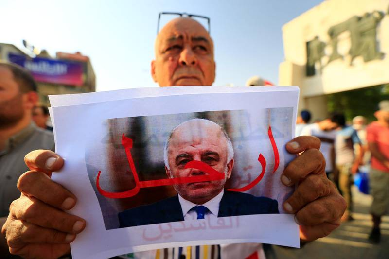 """A protester holds a picture of Iraqi Prime Minister Haider al-Abadi with """"Step Down"""" written on it during a protest at Tahrir square in Baghdad, Iraq July 27, 2018. REUTERS/Thaier al-Sudani"""