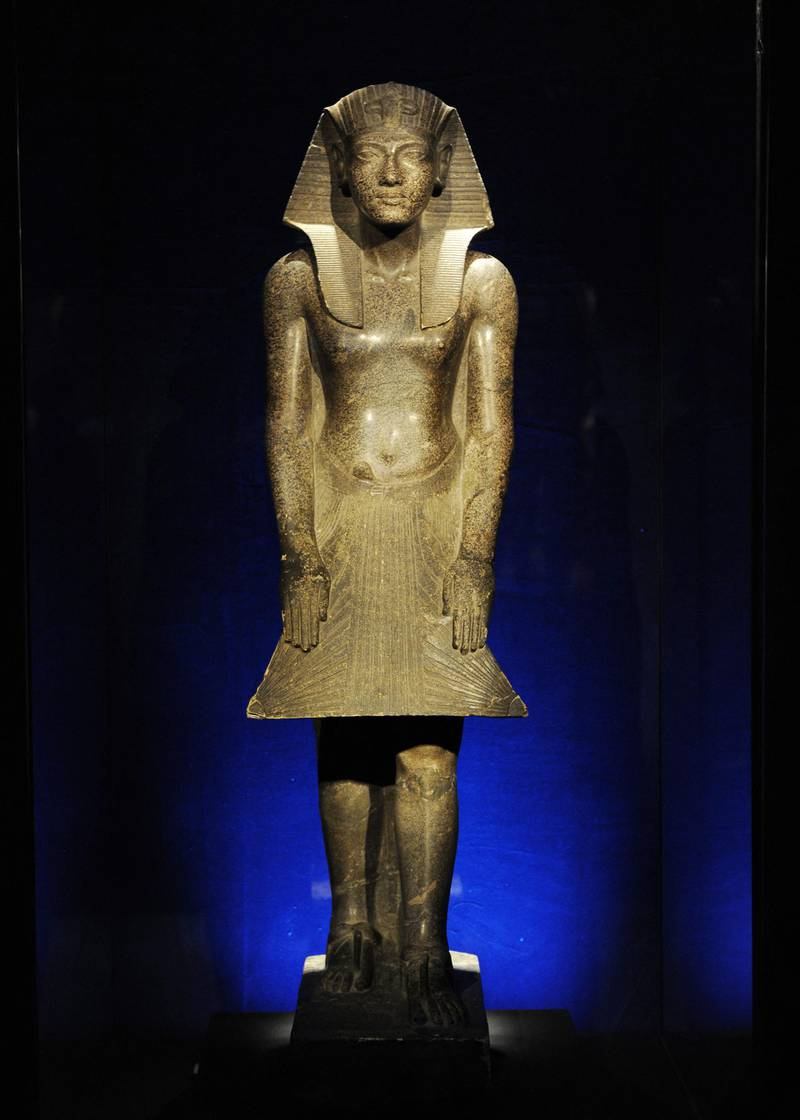 """Detail of a granite statue of Tutankhamun on display April 21, 2010 at a preview of """"Tutankhamun and the Golden Age of the Pharaohs"""", an exhibition at Discovery Times Square Exposition in New York. Multicolored medical scans of the real mummy are reflected in the glass case. The exhibit opens April 23. AFP PHOTO/Stan Honda (Photo by STAN HONDA / AFP)"""