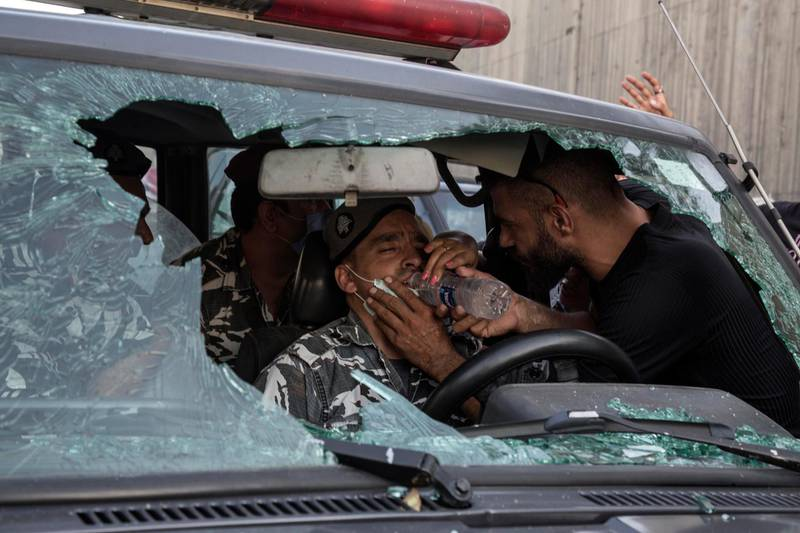 BEIRUT, LEBANON - SEPTEMBER 12: An anti-government protester gives water to a policeman after other protesters attacked his vehicle during a march toward the Presidential Palace, on September 12, 2020 in Baabda, Beirut, Lebanon. (Photo by Sam Tarling/Getty Images)