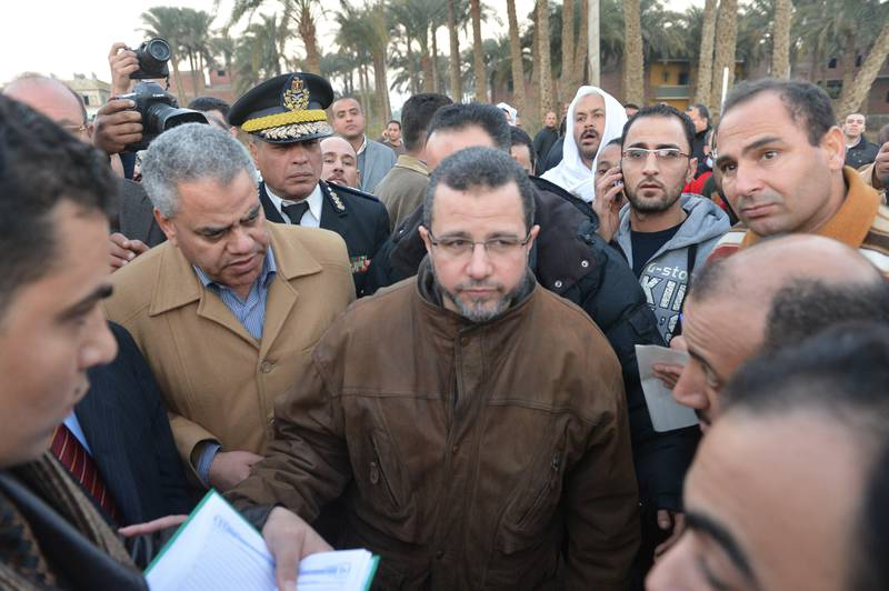 Egyptian Prim Minister Hisham Kandel (C) visits the site of the wreckage of a train in the Giza in Badrashin, about 40 km south of Cairo, on January 15, 2013, at least 19 people where killed and injured 105. The train carrying conscripts from south Egypt to Cairo derailed in the Giza neighbourhood of Badrasheen, state media reported. Giza governor Ali Abdelrahman said emergency services were at the scene and ambulances were ferrying the injured to hospital. The accident is the latest in a string of transport disasters plaguing the country.     AFP PHOTO / KHALED DESOUKI  *** Local Caption ***  260175-01-08.jpg