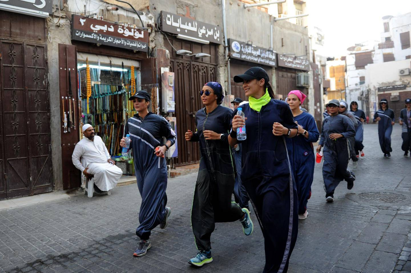 Saudi women jog in the streets of Jeddah's historic al-Balad district on March 8, 2018. Colourful and oozing defiance, a sports-friendly version of the abaya gown was once considered a symbol of cultural rebellion in conservative Saudi Arabia, but it is fast becoming the new normal. / AFP PHOTO / Amer HILABI
