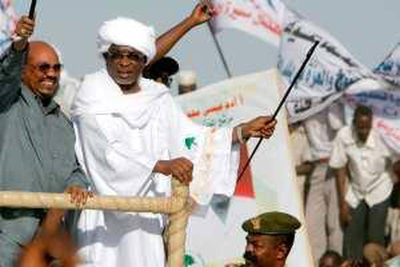 """Sudanese President Omar al-Beshir (L) waves his trademark cane as he rides at the back of vehicle with governor Yussef Kaber (R) during a rally in El-Fasher, the capital of North Darfur state, on February 24, 2010. """"The war in Darfur is over,"""" Beshir said in a speech in the war-torn region, adding that 57 members of a key rebel group, 50 on death row, had been freed. AFP PHOTO/ASHRAF SHAZLY"""