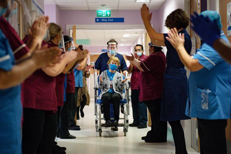 Margaret Keenan (C), 90, is applauded by staff as she returns to her ward after becoming the first person to receive the Pfizer-BioNtech Covid-19 vaccine at University Hospital in Coventry, central England, on December 8, 2020. - Britain on December 8 hailed a turning point in the fight against the coronavirus pandemic, as it begins the biggest vaccination programme in the country's history with a new Covid-19 jab. (Photo by Jacob King / POOL / AFP)