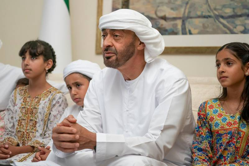 """ABU DHABI, UNITED ARAB EMIRATES - May 19, 2020: HH Sheikh Mohamed bin Zayed Al Nahyan, Crown Prince of Abu Dhabi and Deputy Supreme Commander of the UAE Armed Forces (2nd R), participates in an online lecture by HE Obaid Rashid Al Shamsi, Director-General of the National Emergency Crisis and Disaster Management Authority, titled """"Honoring Our Traditions, Valuing Our Safety"""". The lecture was broadcast on Al Emarat Channel as part of the Ramadan lecture series of Majlis Mohamed bin Zayed. Seen with HH Sheikha Shamma bint Khaled bin Mohamed bin Zayed Al Nahyan (R), HH Sheikh Mohamed bin Nahyan bin Saif Al Nahyan (3rd R) and HH Sheikha Fatima bint Mohamed bin Hamad bin Tahnoon Al Nahyan (4th R).  ( Hamad Al Kaabi / Ministry of Presidential Affairs ) ---"""