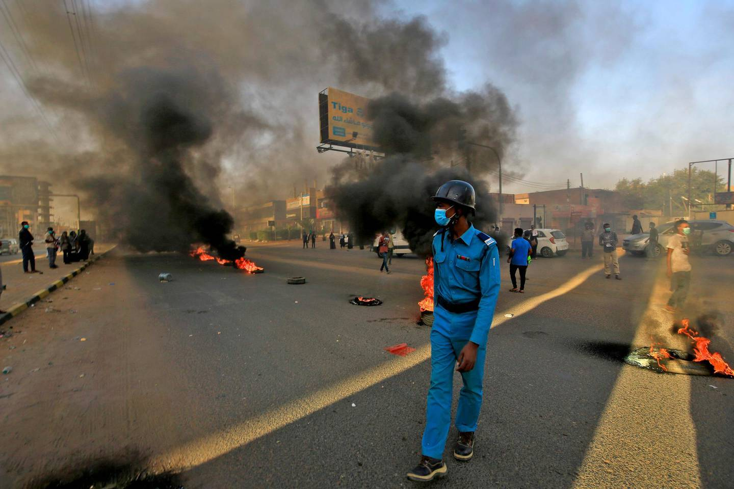 TOPSHOT - A mask-clad policeman walks near tires set aflame by Sudanese protesters marking the first anniversary of a raid on an anti-government sit-in, in the Riyadh district in the east of the capital Khartoum on June 3, 2020. Scores of protesters were killed when armed men in military fatigues stormed the sprawling encampment outside Khartoum's army headquarters on June 3 last year. / AFP / ASHRAF SHAZLY