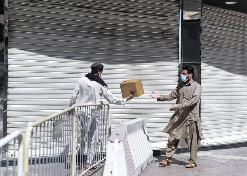 DUBAI, UNITED ARAB EMIRATES. 31 MARCH 2020. A man delivers bread across the barricade set at Al Ras neighborhood. Dubai's Supreme Committee of Crisis and Disaster Management announced increased restrictions on movement in Al Ras area of Dubai for two weeks effective from today to facilitate intensified sterilisation procedures. @DubaiPoliceHQ appeals to the public to cooperate fully with the authorities and abide by all instructions to ensure the preventive measures implemented during the two-week period are a success. People who are not residents of Al Ras are prohibited from travelling to the area.RTA closed entrances leading to Al Ras area from three main roads and interchanges: Al Musalla, Al Khaleej, and Baniyas Streets. The plan also includes the closure of three stations on the metro green line: Al Ras, Palm Deira and Baniyas Square.(Photo: Reem Mohammed/The National)Reporter: NICK WEBSTERSection: COVID NA