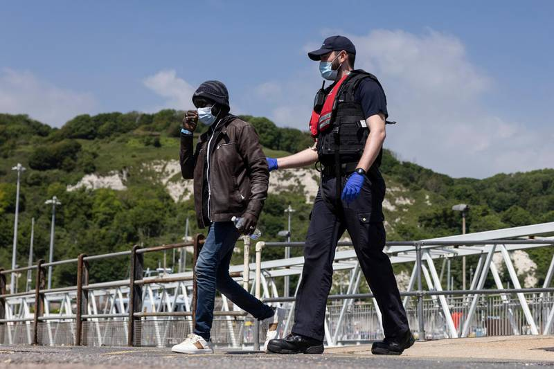 DOVER, ENGLAND - JUNE 24: Border Force officials guide newly arrived migrants to a holding facility after being picked up in a dinghy in the English Channel on June 24, 2021 in Dover, England. More than 5,000 migrants have arrived this year by crossing the English Channel in boats. (Photo by Dan Kitwood/Getty Images)
