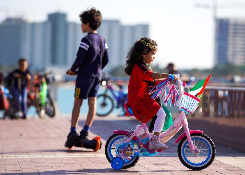 Abu Dhabi, United Arab Emirates, December, 2, 2020.   Children on their scooters with UAE flags and other UAE Day paraphernalia along ther Corniche.Victor Besa/The NationalSection:  National News