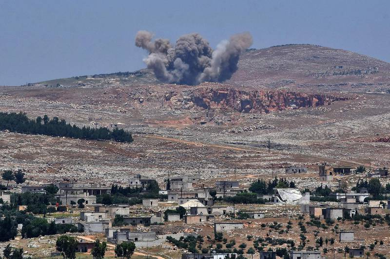 TOPSHOT - This picture taken on May 17, 2019 from the Syrian town of Qalaat al-Madiq, some 45 kilometres northwest of the central city of Hama, shows bombardment by Syrian government forces on the Shashabo Mountain.  / AFP / George OURFALIAN
