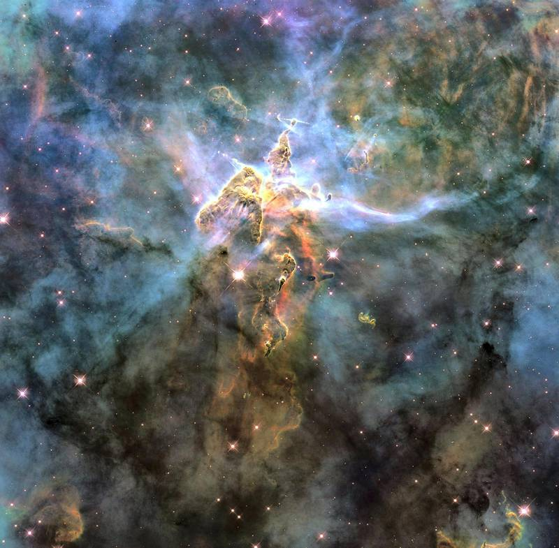 The NASA Hubble Space Telescope photograph, which is stranger than fiction, captures the chaotic activity atop a three-light-year-tall pillar of gas and dust that is being eaten away by the brilliant light from nearby bright stars. The pillar is also being assaulted from within, as infant stars buried inside it fire off jets of gas that can be seen streaming from towering peaks. This turbulent cosmic pinnacle lies within a tempestuous stellar nursery called the Carina Nebula, located 7,500 light-years away in the southern constellation Carina. NASA