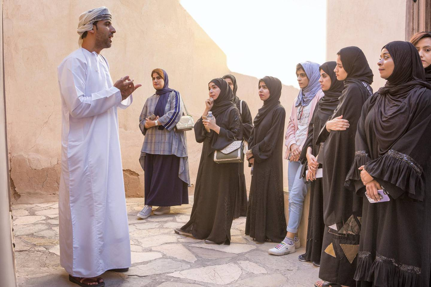 A group of female Omani diploma students practice tour guiding with Bader Thuhli, a professor of tour guiding at the Oman Tourism College, the only college in the Sultanate of Oman specializes Tourism & Hospitality.