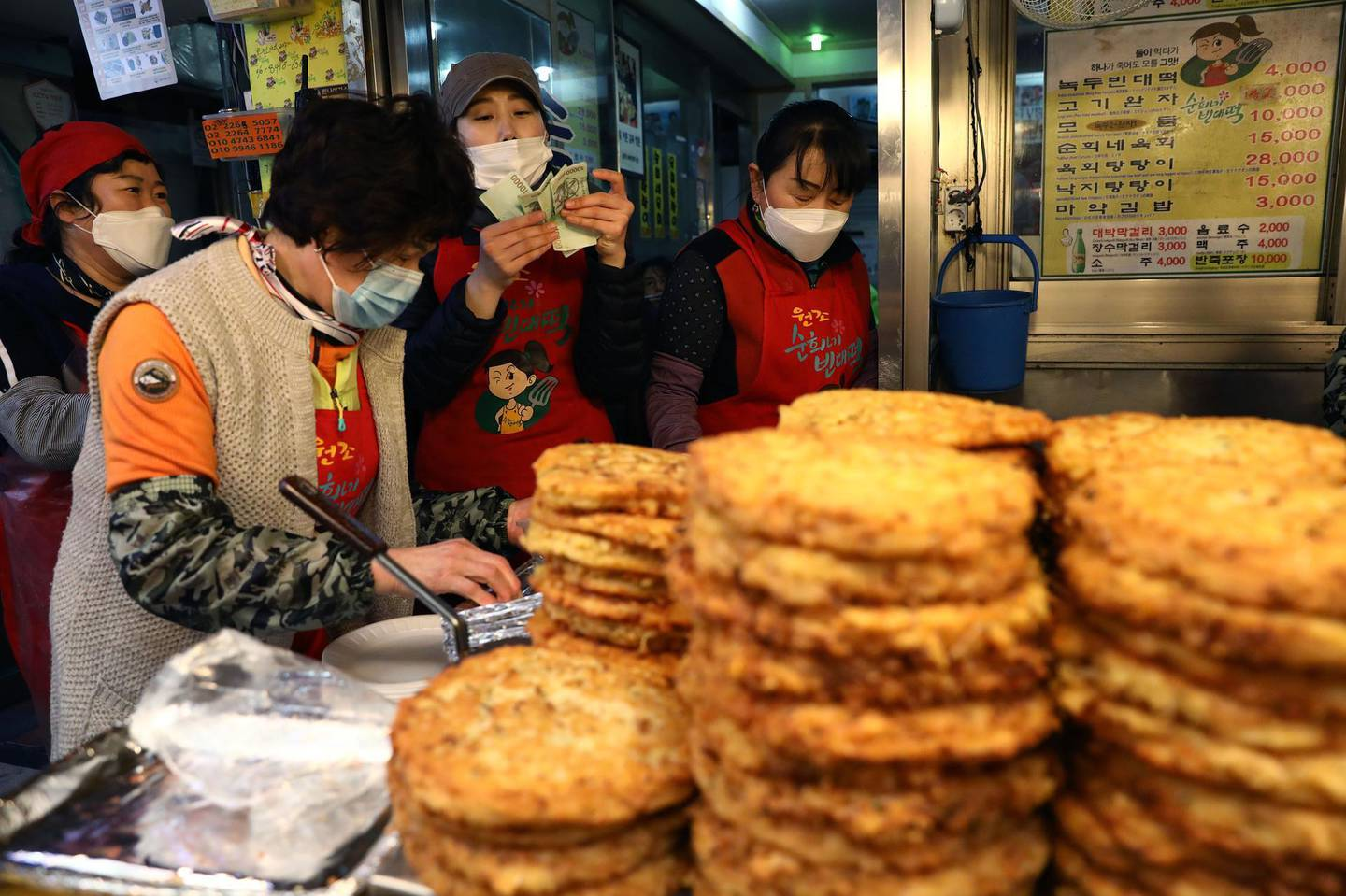 SEOUL, SOUTH KOREA - APRIL 12: Shopkeepers wear masks as they wait for a customer during a Easter holiday Kwangjang market during a Easter as South Koreans take measures to protect themselves against the spread of coronavirus (COVID-19) on April 12, 2020 in Seoul, South Korea. South Korea has called for expanded public participation in social distancing, as the country witnesses a wave of community spread and imported infections leading to a resurgence in new cases of COVID-19. South Korea's coronavirus cases hovered around 30 for the third straight day Sunday, but health authorities are still staying vigilant over cluster infections, as well as new cases coming from overseas. According to the Korea Center for Disease Control and Prevention on Sunday, 32 new cases were reported. The total number of infections in the nation tallies at 10,512. (Photo by Chung Sung-Jun/Getty Images)