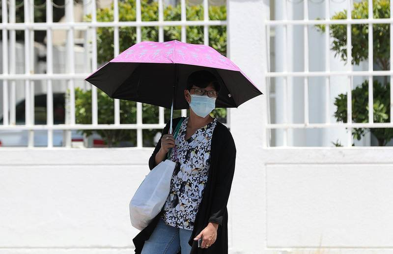 Dubai, United Arab Emirates - Reporter: N/A. News. Weather. A women walks to the bus stop with an umbrella on a hot day. Tuesday, June 23nd, 2020. Jumeriah, Dubai. Chris Whiteoak / The National